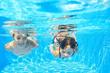 Happy girls swim underwater in pool, having fun on vacation