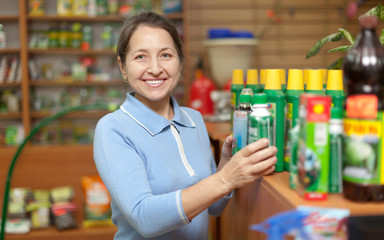 woman chooses agricultural chemicals at shop for gardeners