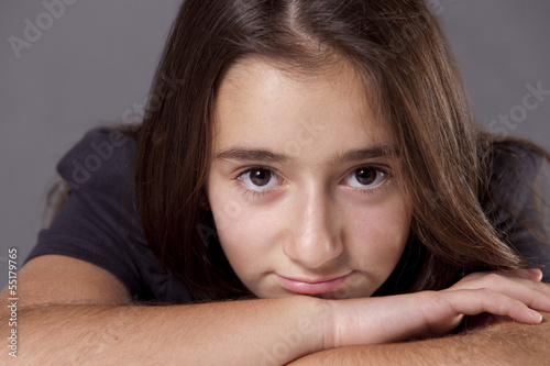 Young teenage girl, looking at camera pensively.