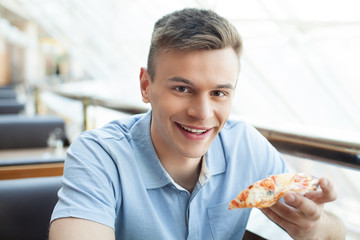 Man eating pizza. Cheerful young man eating pizza at the restaur