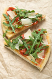 Two pieces of pizza with arugula