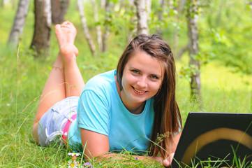 Молодая девушка с ноутбуком в лесу