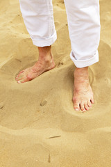 Feet of senior man standing in sand. Wearing white pants.
