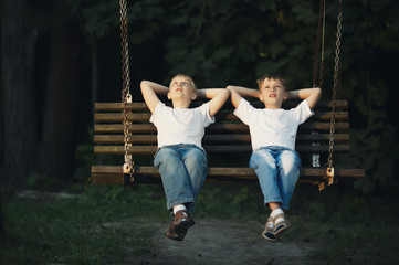 little boys riding on swing