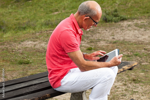 Retired senior man resting and using his tablet at table in park