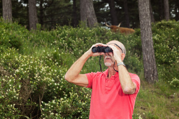 Senior retired man with beard using binoculars outdoors. Wearing