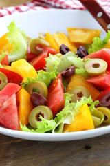 salad of colorful tomatoes and olives on the wooden table