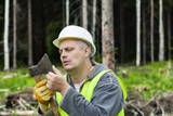 Lumberjack checking ax sharpness in forest