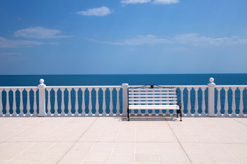 white bench, balustrade and empty terrace overlooking the sea