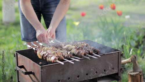 Young man cooking kebabs on the grill outdoors