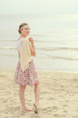 Young woman with scarf standing on a sea shore