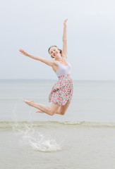 Young happy woman jumping on a sea shore