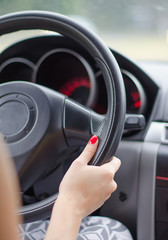 Female driver's hands on a steering wheel of a car
