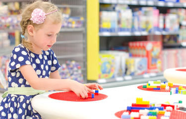 Cute little girl playing with blocks in supermarket