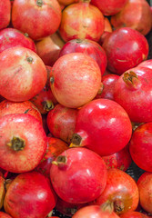 Lot of red fresh pomegranates closeup view