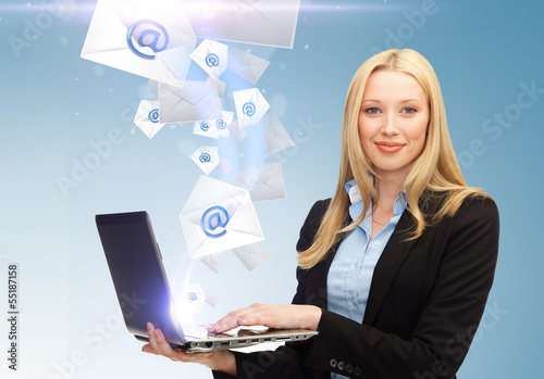 businesswoman holding laptop with email sign