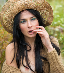 Emotional nude woman in straw hat