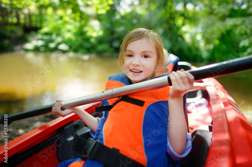 Happy little girl on a kayak on a river