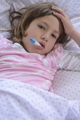 Child with fever in bed