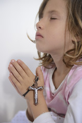 Child praying with cross