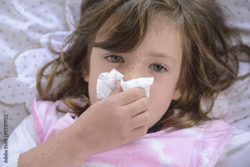 Sneezing ill child in bed