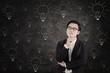 Asian businessman concentrating on lightbulbs blackboard
