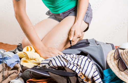 Woman packing overfilled travel bag