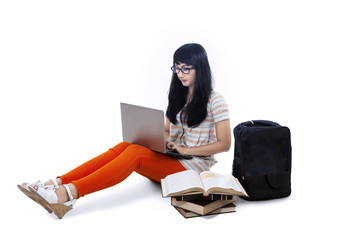 Asian female student typing on laptop - isolated