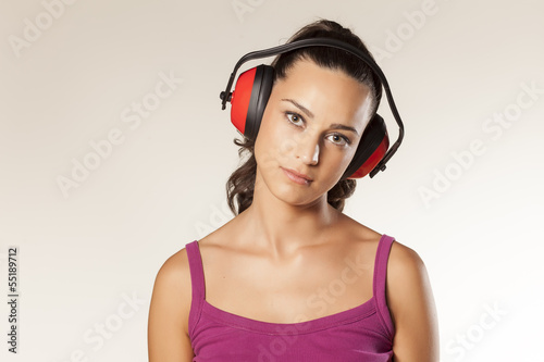 beautiful young brunette posing with anti loud headset