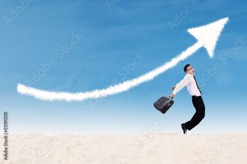 Businessman jumping under profit arrow sign