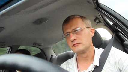 A man wearing glasses while driving.