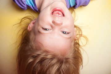 Little girl upside down against yellow background