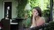 Beautiful woman sitting in a garden and talking on cell phone
