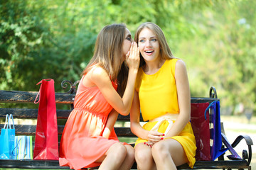 Two beautiful young woman with shopping bags in park