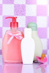 Baby cosmetics in bathroom on violet tile wall background