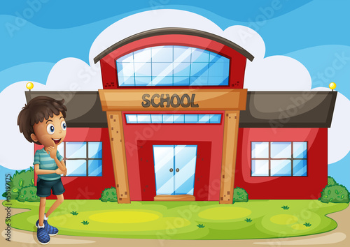 A boy in front of the school building