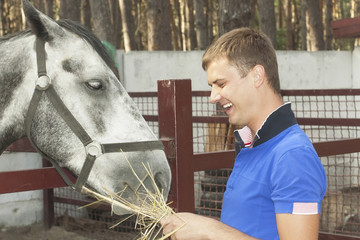 young guy feeding horse