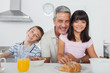 Siblings eating breakfast in kitchen together with dad