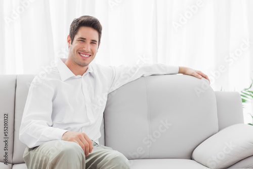 Stylish young man sitting on sofa