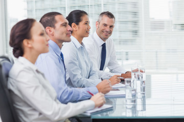 Businessman smiling at camera while his colleagues listening