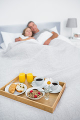 Cuddling couple sleeping with breakfast tray on bed