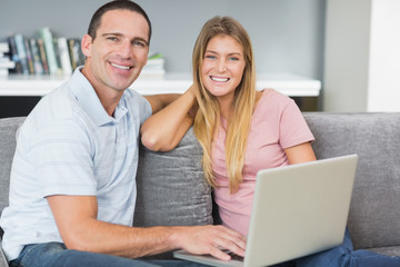 Smiling couple sitting using laptop on the couch together