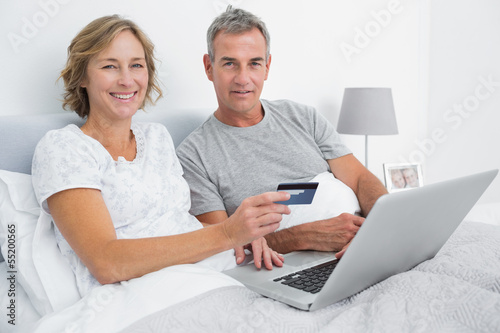 Smiling couple using their laptop to buy online