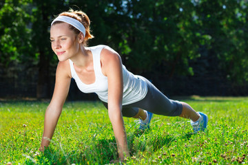 Young woman doing push ups on green grass.