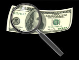 Hundred dollar bill and magnifying glass isolated on black