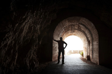 Young man stands relaxed in dark tunnel