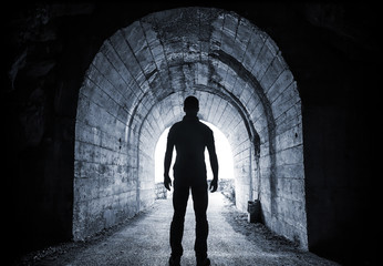 Man stands in dark tunnel and looks in glowing end