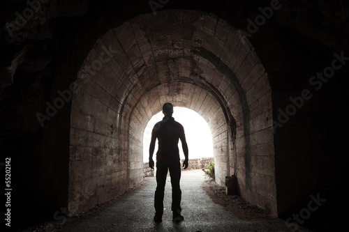 Young man stands in dark tunnel and looks out