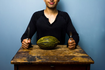 Healthy young man having a melon for dinner
