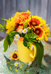 Garden flowers in yellow mug